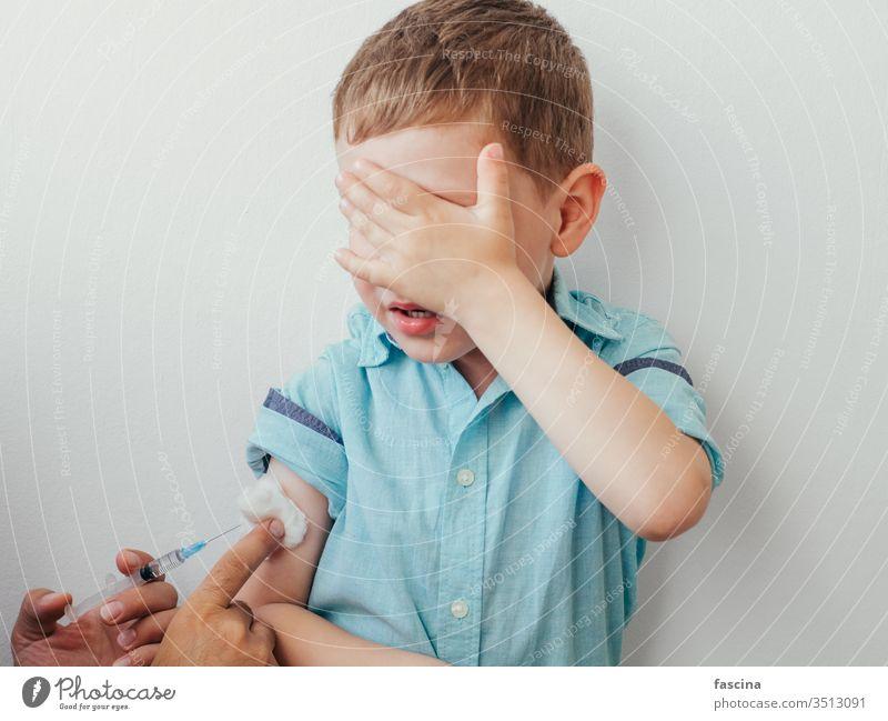 Kleiner Junge hat Angst vor dem Impfen wenig ängstlich impfen Impfstoff Kaukasier Einspritzung Kind weiß bedeckt Auge blau Hemd Hand während Impfung Kinder