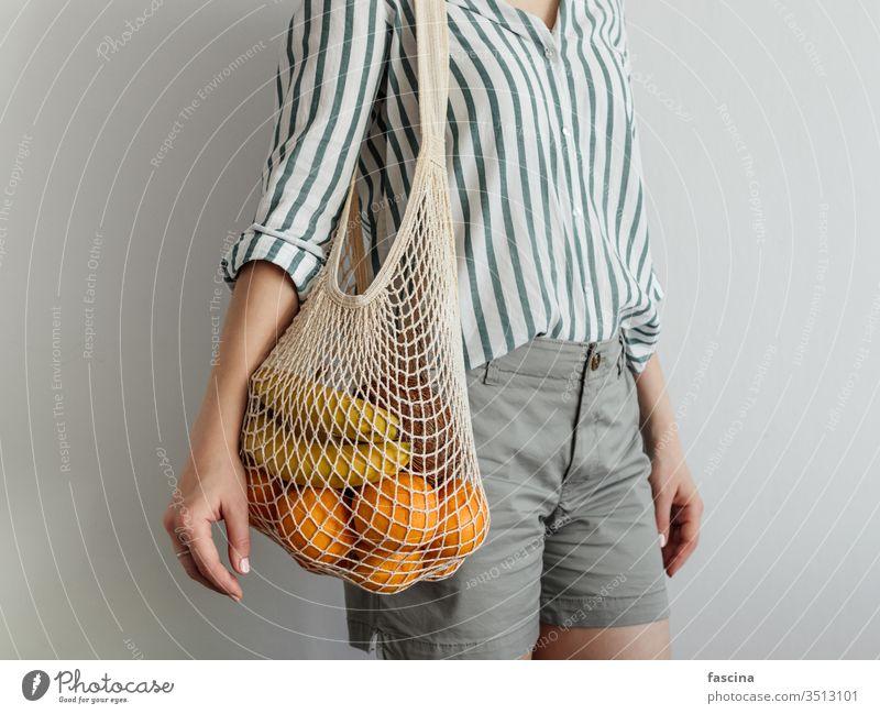 Frau stehend mit Netztasche auf der Schulter ineinander greifen Tasche keine Verschwendung null Abfall Früchte kaufen lässig Stil modern Konzept Gewebe Frucht