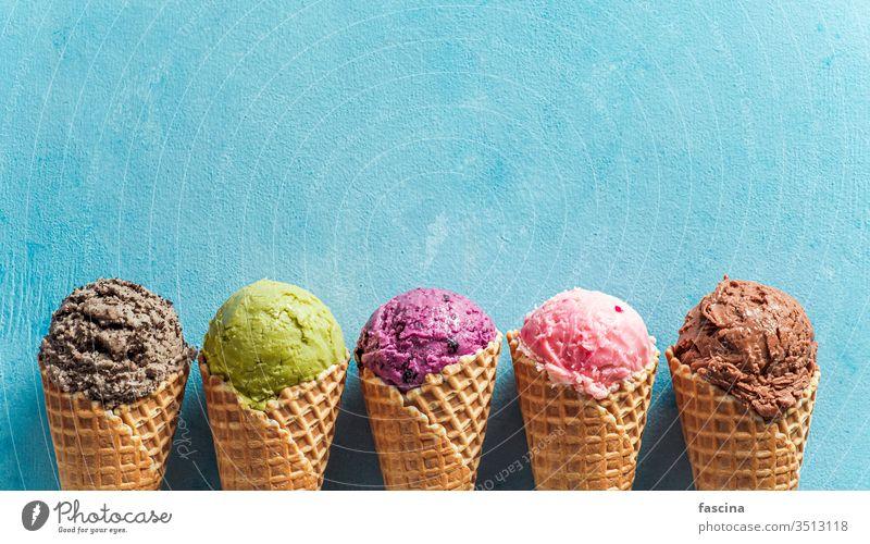 Eiskugeln in Tüten mit Kopierfeld auf blau Sahne Zapfen Speiseeis gelato Eisbecher Textfreiraum Schaufeln Transparente Hintergrund Sommer oben Ball Kekse