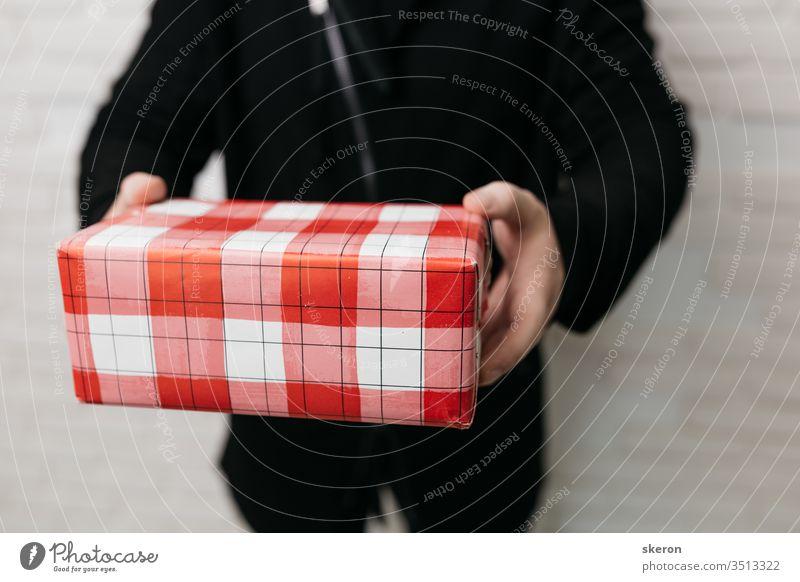 junger dunkelhaariger mann liefert eine geschenkbox während einer coronavirus-epidemie. konzept: kontaktlose kurierlieferung. typ mit medizinischer maske und frühlingsstraßenkleidung: schwarze jacke. Denken Sie an Ihre Gesundheit.
