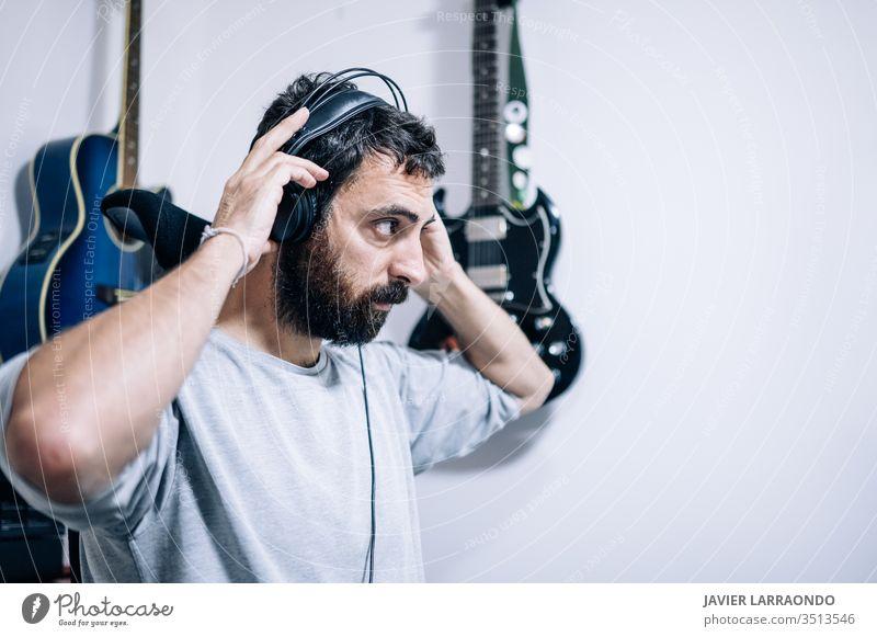 Arbeitender Toningenieur mit Kopfhörer im Heimstudio. Mann Komponist Lernen Gitarren Künstler Audio Rücken Hintergründe digital Entertainment Computer