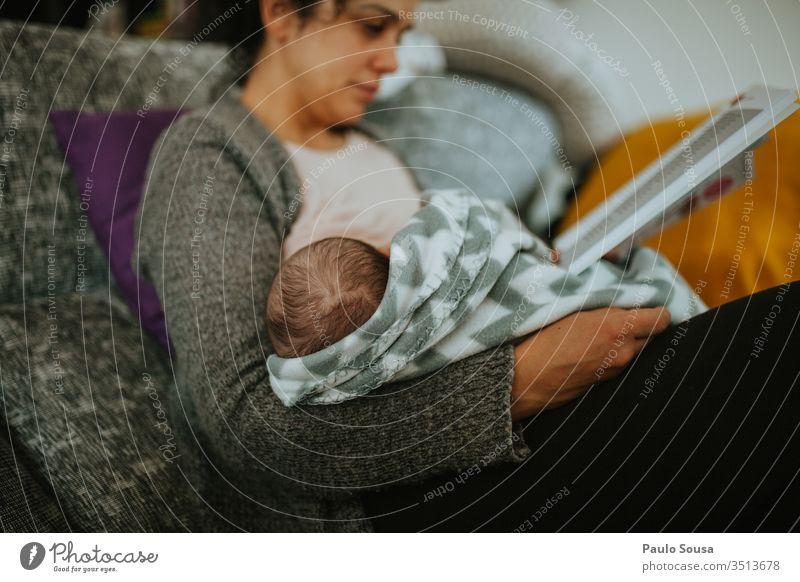 Mutter stillt während sie ein Buch liest Mutterschaft Krankenpflege stillen Mutterliebe Mutter mit Kind Liebe Erwachsene Familie & Verwandtschaft Glück Pflege