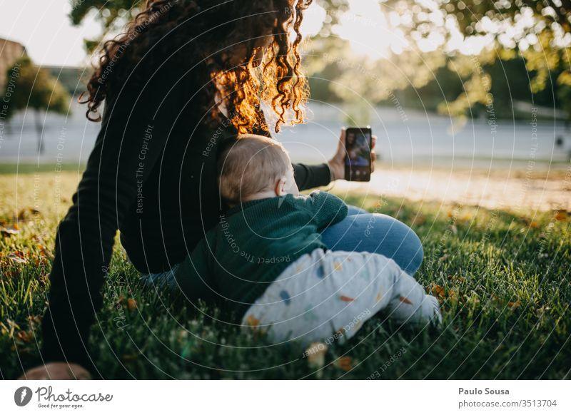 Mutter und Baby beim Selbstauslöser-Foto Technik & Technologie Smartphone Selfie fotografierend Zusammensein Lifestyle Leben Freude Lächeln Außenaufnahme