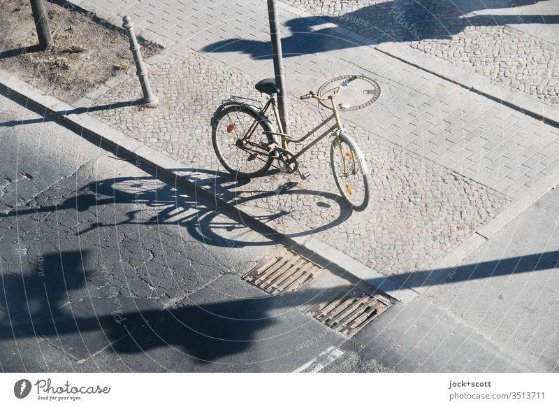 mit langen Schatten zentral abgestellt Fahrrad Asphalt Straße Verkehrswege angeschlossen Pfahl Bürgersteig Kopfsteinpflaster Risse Bordsteinkante abstrakt Gully