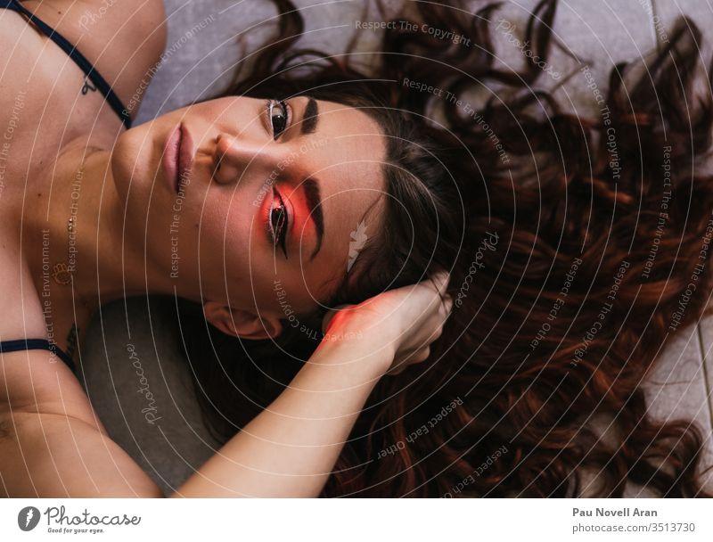 Nahaufnahme einer sinnlichen, jungen, hübschen Frau, die mit langen, zerzausten Haaren auf dem Boden liegt Behaarung fliegen Aufstrich Rotschopf oben attraktiv