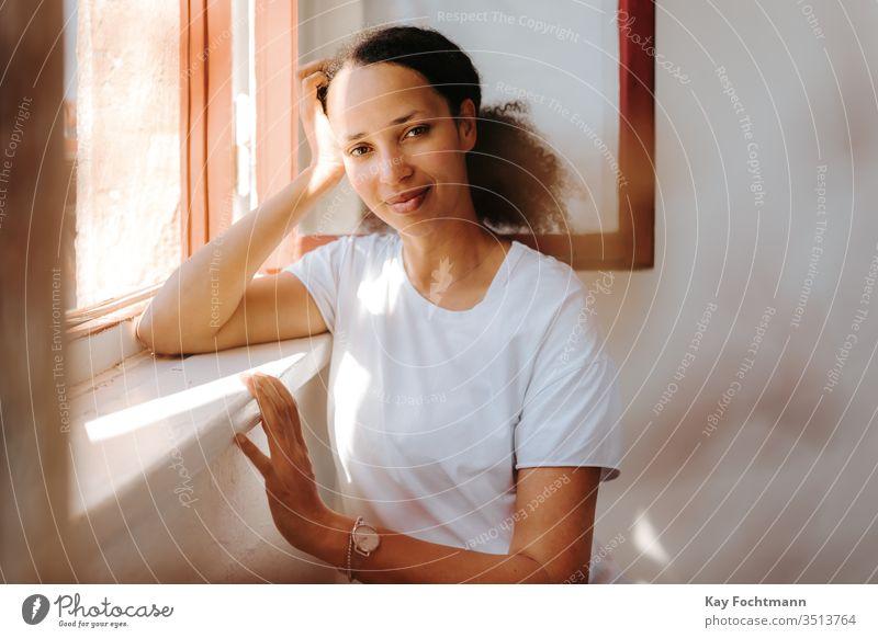 verträumte schwarze Frau, die am Fenster lehnt 25-30 Erwachsener Afroamerikaner attraktiv schön Schönheit lockig Tag ethnisch Ethnizität Behaarung Glück