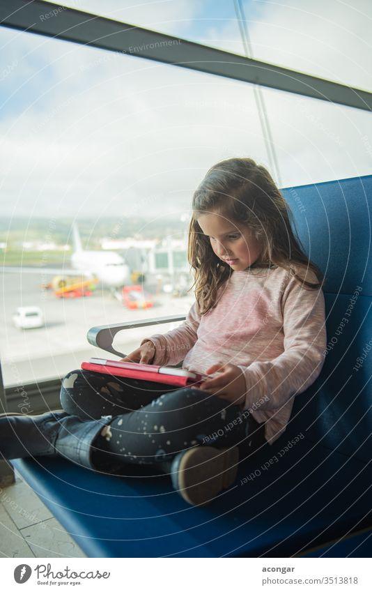 Kleines süßes Mädchen wartet am Flughafenterminal auf das Flugzeug und benutzt ein digitales Tablett Kind bezaubernd Fluggerät Fluggesellschaft Kaukasier Stuhl
