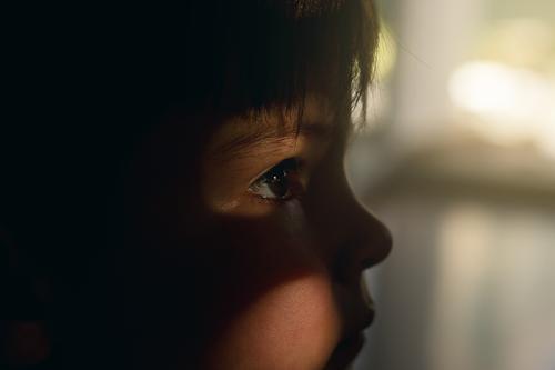 kleiner Junge mit Lichteinfall auf Auge einsamkeit alleine kleinkind junge auge lichteinfall sonnenlicht hoffung träumen sehnsucht hilfesuchend Sorgen Angst