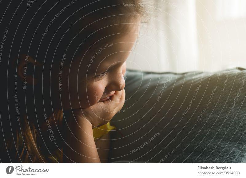 Kleines Mädchen, auf Sofa sitzend, schaut träumend aus dem Fenster mädchen kleinkind aus dem fenster schauen gemütlich zuhause nachdenklich