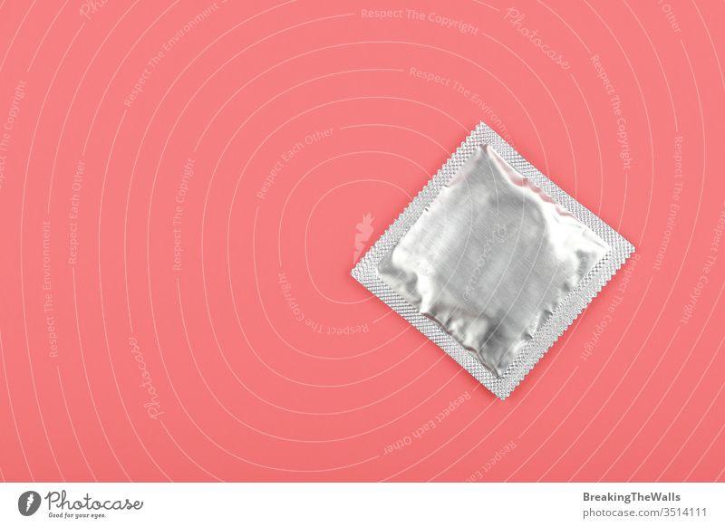 Nahaufnahme eines Kondompaketes über rosa Hintergrund Rudel Silber Folie umhüllen Pastell erhöht hoch Winkel Top Ansicht direkt oben Kopie Raum schließen