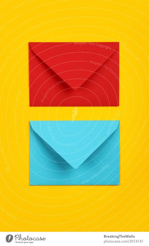 Zwei geschlossene Umschläge aus blauem und rotem Papier auf gelb Kuvert zwei Pastell lebhaft Hintergrund Nahaufnahme Farbe farbenfroh mehrfarbig schließen