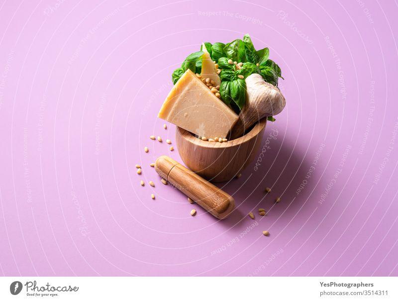 Grüne Pestozutaten in einem Mörser. Herstellung von Pestosauce Italienisch authentisch Basilikumblätter Käse farbenfroh Essen zubereiten Küche Dip Dressing