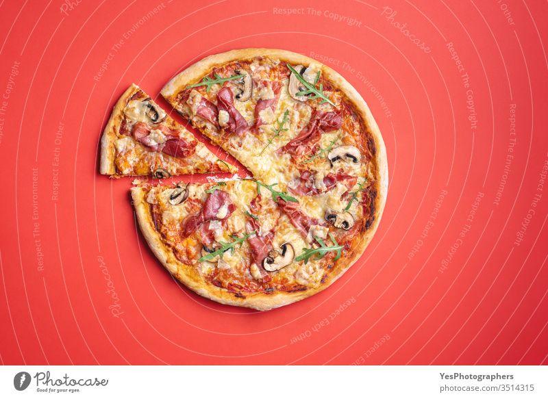 Schinken-Pizza hausgemacht. Pizza-Draufsicht auf rotem Hintergrund. obere Ansicht Rucola Bäckerei champignons Käse Komfortnahrung Kruste Küche ausschneiden
