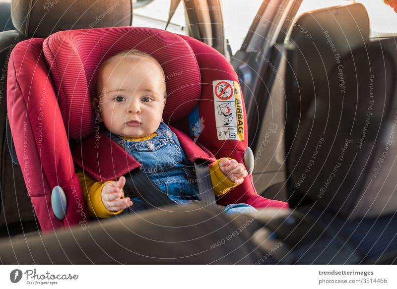 Vater schnallt sein Baby im Autositz an isofix Schnappriegel PKW Sitz Kind befestigen Sicherheit Gurt Schutz Transport Fahrzeug Familie reisen Menschen Glück