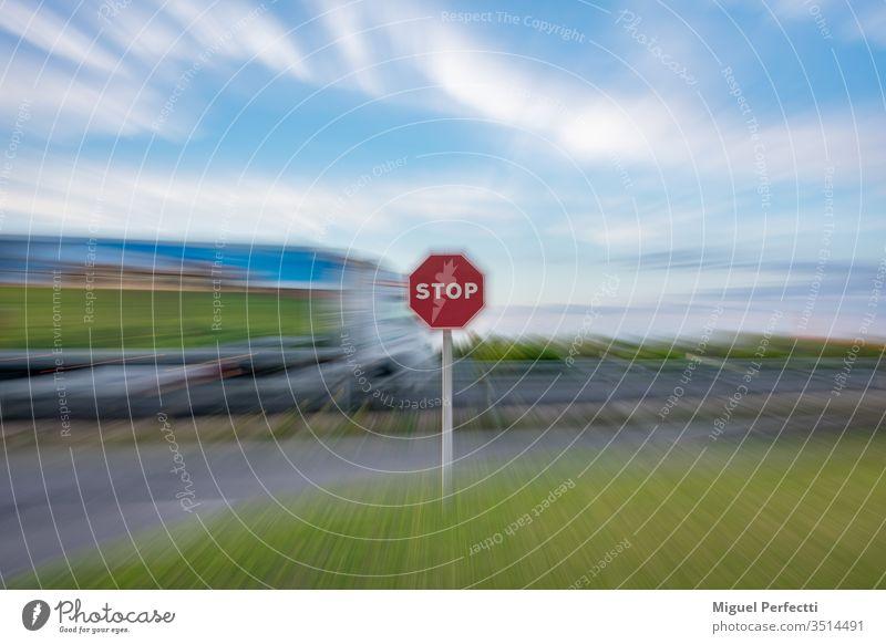 """""""Stopp""""-Verkehrszeichen und ein fahrender Lastwagen auf der Straße, alles unter einem Zoom-Effekt Verkehrsgebot stoppen Zeichen Stoppschild Symbol Ermahnung"""