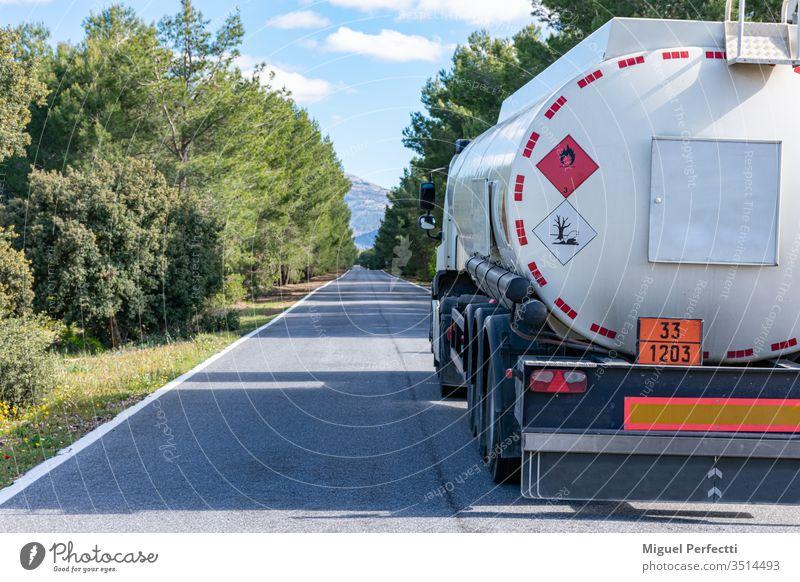 Gefahrzettel für brennbare und umweltschädliche Flüssigkeiten auf einem Tankwagen, der auf einer schmalen, geraden, von Bäumen gesäumten Straße fährt.
