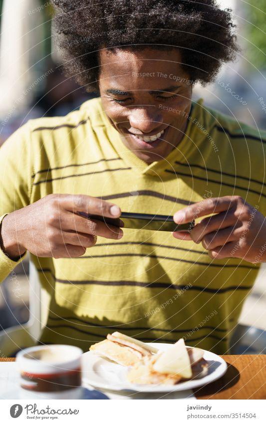 Kubanischer Schwarzer beim Fotografieren mit seinem Smartphone zu einem Imbiss Mann Afro-Look schwarz Behaarung Afrikanisch tausendjährig männlich Person lässig