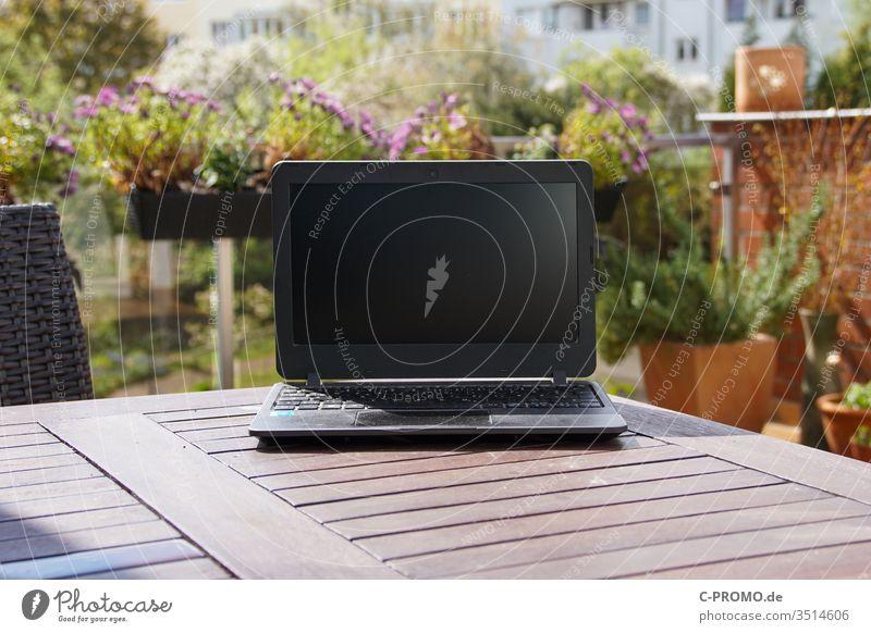 Laptop auf Terrassentisch vor Blumen Notebook Computer Outdoor Balkon Blumenkasten Homeoffice Frühling draußen arbeiten Büro