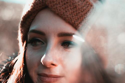 Nahaufnahme einer attraktiven Brünetten in Winterkleidung und orangem Stirnband. Kalter Wintertag im Wald, ernstes fröhliches Gesicht, das in die Ferne schaut und denkt
