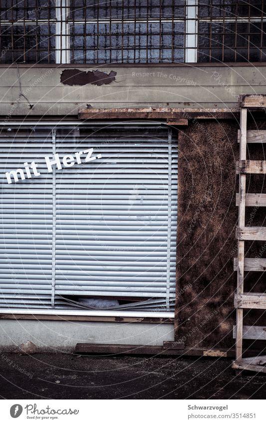 bröckelnde Fassade mit Herz Verfallen Leerstand verlassen Geschäft geschäftsaufgabe Jalousien Schriftzug Konkurs