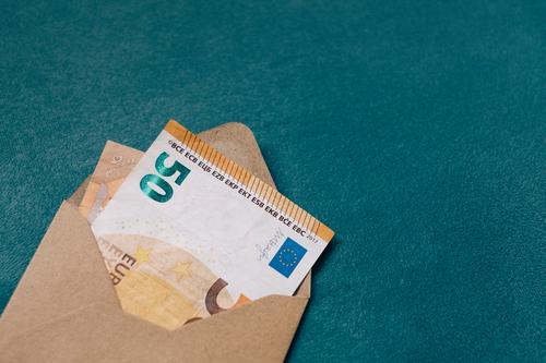 Ein brauner Umschlag in dem ein Geldschein steckt 50er 50 Euro Schein Geschenk schenken Geldgeschenk Rechnung Post Innenaufnahme sparen Menschenleer