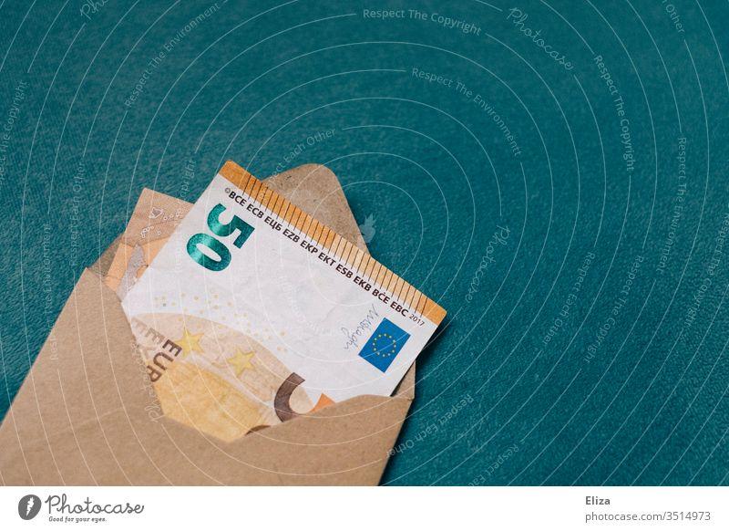 Ein brauner Umschlag in dem ein Geldschein steckt. Rendite. Gewinn. Geldgeschenk. 50er 50 Euro Schein Geschenk schenken Rechnung Post Innenaufnahme sparen