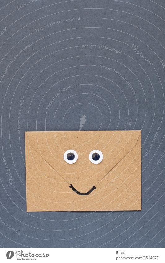 Ein brauner freundlich lächelnder Briefumschlag mit Augen und Mund Wackelaugen gute Nachrichten Freude Gesicht Lächeln Post Umschlag Kommunizieren Kommunikation