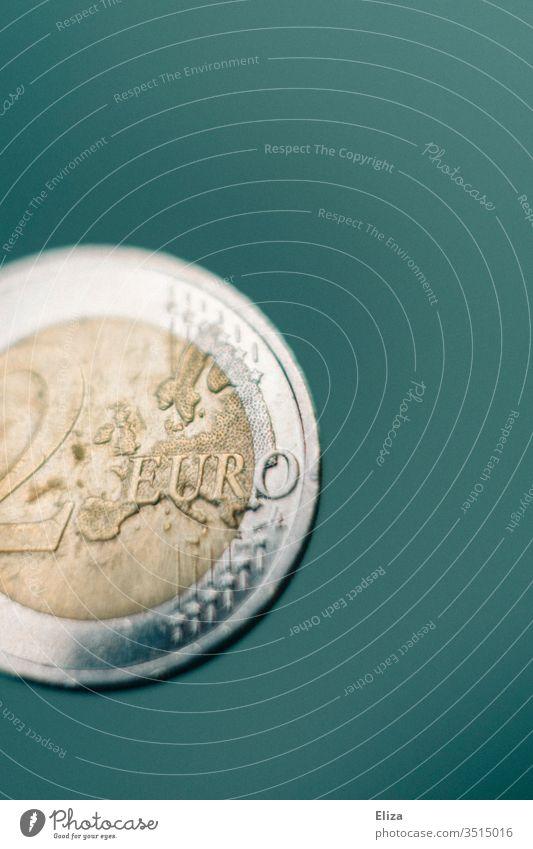 Nahaufnahme einer Zwei Euro Münze vor türkisem Hintergrund; Geld, Finanzen Makroaufnahme Eurostück hell Finazen Sparen Kapitalwirtschaft Geldmünzen Bargeld