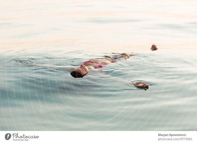 Junge Frau schwebt bei Sonnenuntergang im Meer aquatisch schön Schönheit blau Kaukasier übersichtlich genießend Genuss exotisch fliegend Spaß Mädchen Glück