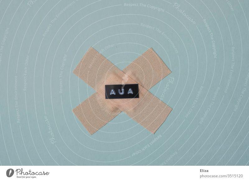 Zwei Pflaster auf denen das Wort Aua geschrieben steht; Schmerz, Verletzung verarzten Wunde Unfall Gesundheitswesen blau Hintergrund neutral Heftpflaster