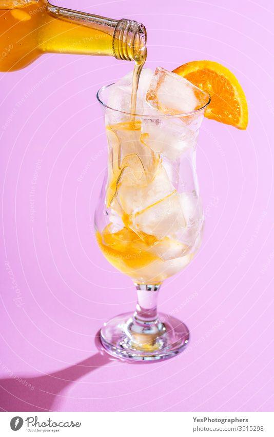 Gießen Sie Orangensirup in ein Glas mit Eiswürfeln. Limonade herstellen Getränk hell Nahaufnahme Cocktail Erfrischungsgetränk farbenfroh lecker Entzug