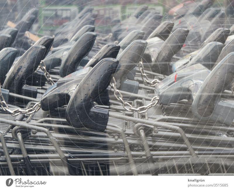 Schwarze Griffe von Einkaufswagen die miteinander verbunden sind zusammen Kettenglied Metall Reflexion & Spiegelung Farbfoto Außenaufnahme Menschenleer