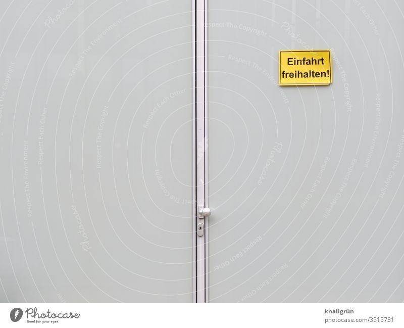 """Große Doppeltür mit """"Einfahrt freihalten"""" - Schild rechts oben Schilder & Markierungen Tür Tor Hinweisschild Außenaufnahme Warnschild Kommunizieren Mitteilung"""