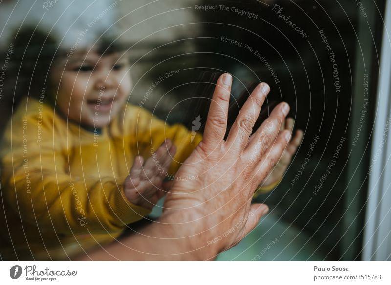 Kind berührt Vaterhand durch Glas Quarantäne Quarantänezeit Coronavirus sars Pandemie COVID covid-19 Prävention Seuche ansteckend infektiös