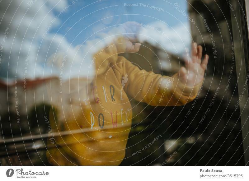 Mädchen hinter Glasfenster Fenster Reflexion & Spiegelung Quarantäne covid-19 Sicherheit Coronavirus Pandemie Schutz Kind heimwärts im Innenbereich zu Hause