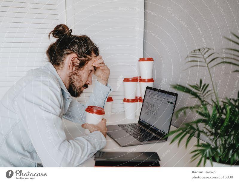 Erschöpfter junger Mann mit Bart sitzt auf dem Stuhl und benutzt einen Laptop. Video-Chat Online-Shopping mit Hilfe von Technologie Verwendung des Laptops