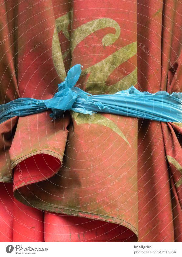 Schmutziger roter Sonnenschirm zusammengebunden mit einem blauen Stoffstreifen dreckig schmutzig Knoten verknotet weiß Außenaufnahme Farbfoto Detailaufnahme