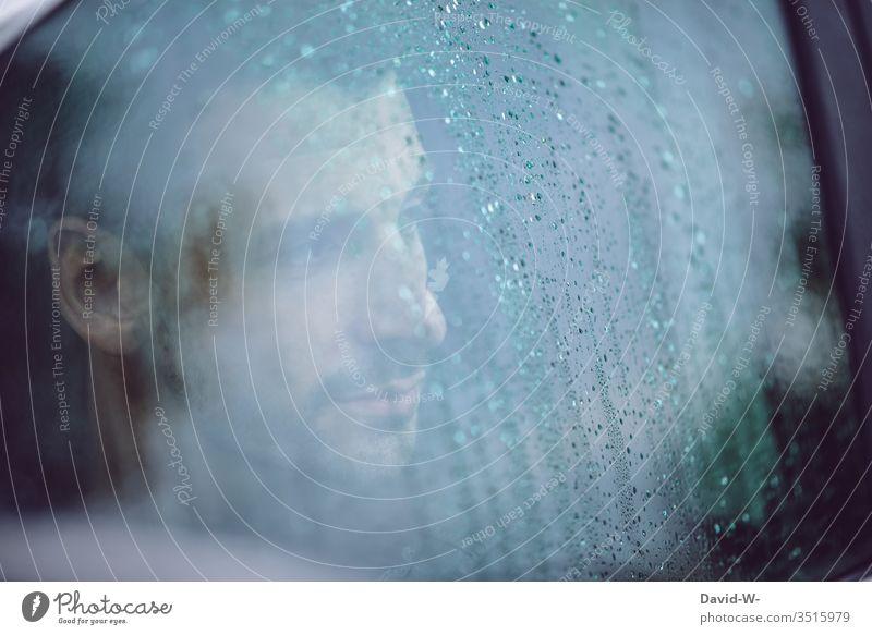 Mann schaut bei Regen aus dem Auto durch das nasse Fenster Blick Autofahren Regenwetter Herbst schlechtes Wetter trüb Trübsal depressiv Straße grau Farbfoto Tag