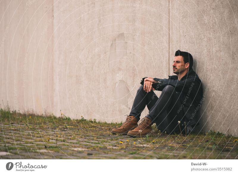 Mann sitzt einsam an einer Wand draußen alleine nachdenklich frustriert Frustration Textfreiraum oben Textfreiraum links Textfreiraum Mitte Model Ruhe sauer