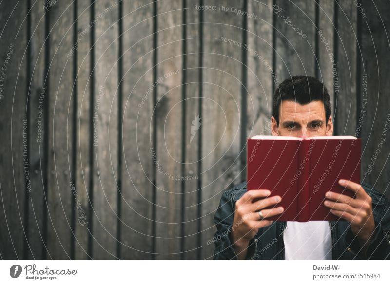 Mann hält vor einer Holzwand ein Buch in den Händen und schaut in die Kamera lesen Bildung gebeildet lernen Lesestoff Buchseite Leser freude Spaß Literatur