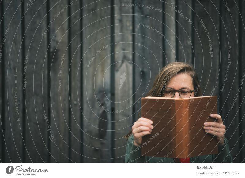 junge Frau mit Brille liest draußen vor einer rustikalen Holzwand ein Buch lesen Bücher dunkel lesend gebildet Bildung interessiert schlau wissensdurstig