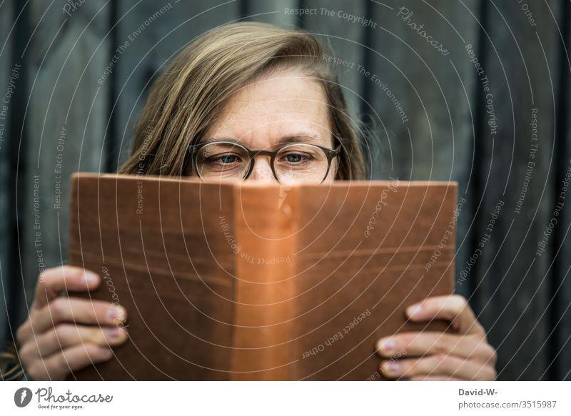 Frau mit Brille hält ein Buch in den Händen und liest lesen jung Leserin vertieft nerdig natürlich spannung Literatur Bildung konzentriert