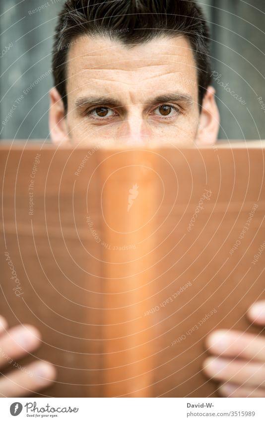 lesen Mann liest Buch Blick in die Kamera Gesicht Textfreiraum unten Textfreiraum Mitte Buchcover neutral leer männlich Leser Lesestoff Leseratte Hände