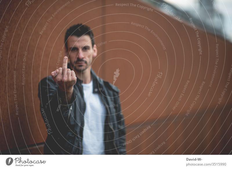 Mann zeigt den Mittelfinger - viel Tetxfreiraum vorhanden zeigen agessionen agressiv agressivität böse angenervt ausstrecken männlich cool Person Menschheit