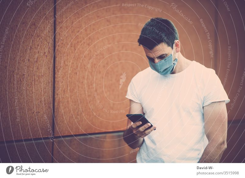 Corona - Mann mit Handy in der Hand Atemschutzmaske coronavirus Virus lesen Manipulation Nachrichtenübermittlung selbstgemacht Mundschutz schreiben Krankheit