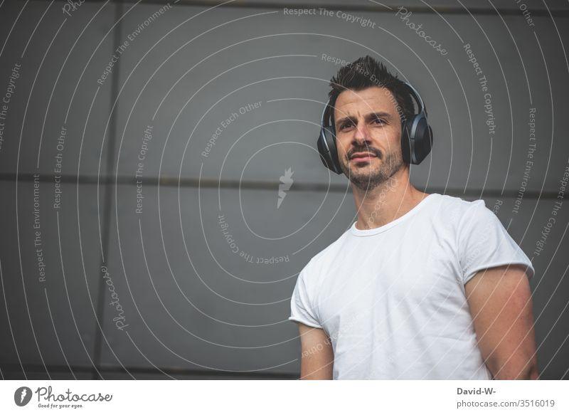 Mann hört Musik über einen Bluetooth Kopfhörer Musik hören kabellos Bluetoothkopfhörer Mensch Porträt Farbfoto Freizeit & Hobby Lifestyle Textfreiraum links