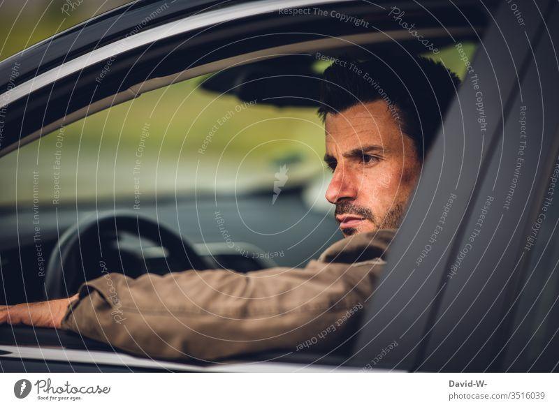 Mann sitzt im Auto und schaut ernst aus dem Fenster blick nach draussen Rückspiegel Spiegel blick zurück Straßenverkehr Autofenster offen genervt sauer böse