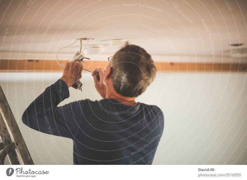 Mann bringt Lampe an Elektrizität Elektriker Energiewirtschaft Kabel Technik & Technologie Draht aufmerksam konzentriert achtsam verantwortungsbewusstsein Strom