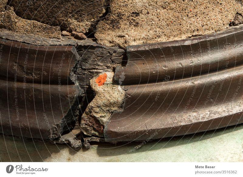 Nahaufnahme eines gerissenen Elements, das zur Reparatur der Basis einer Säule verwendet wurde, wobei Zement- und Ziegelsteinstücke freigelegt wurden.