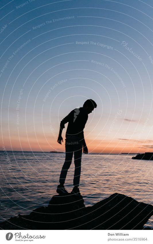Silhouette eines Mannes auf See allein Landschaft Natur Meer jung Abenteuer Hintergrund Wasser blau Wolken Abend Junge Horizont Sonnenuntergang Berge Gipfel